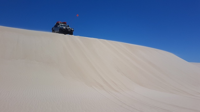 Aaron in his Patrol at the top of a dune.