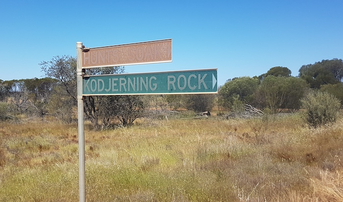These signs are the other side of the road from the well and rock.
