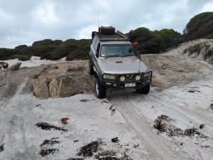Scott takes his Patrol over the rock ledge onto Starvation Harbour Beach.