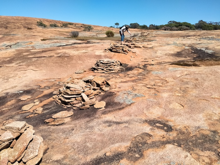 These small cairns were used to hold up fence posts.The fence was to keep animals out of the water supply.